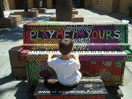 Future pianist plays at a street piano near the Egyptian Theater. Photo by Adam Winter via streetpianos.com