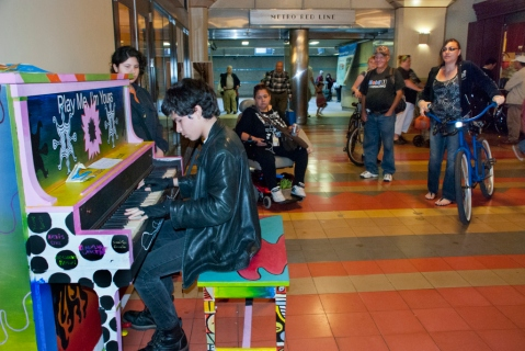 People gather to watch a budding musician at Union Station in Los Angeles. Photo by The MetroDuo Blog
