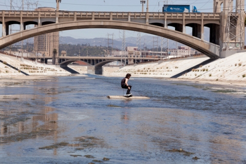Surfer in the Los Angeles River by Calder Greenwood. Photo by Stephen Zeigler via KCET Departures.