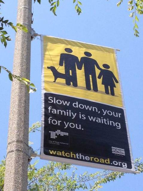 Pedestrian safety ads in West Hollywood, CA feature a same sex family. Photo via Curbed LA